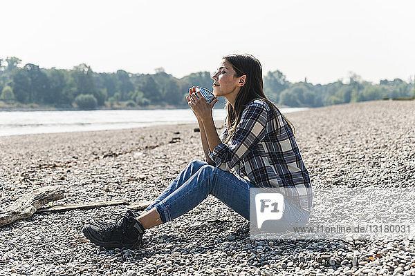 Entspannte junge Frau  die am Flussufer sitzend einen Becher hält
