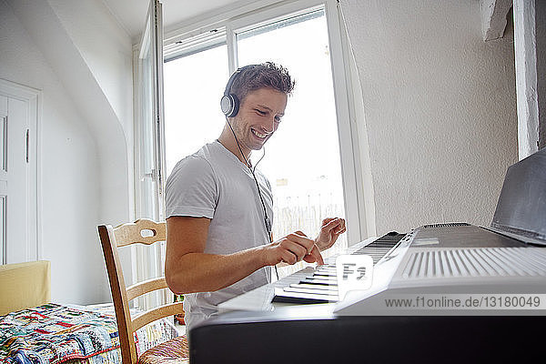 Smiling young man at home wearing headphones playing digital piano