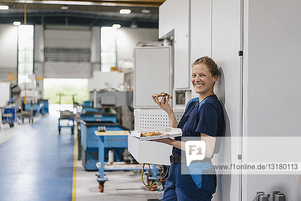 Woman working in high tech company  taking a break  eating pizza