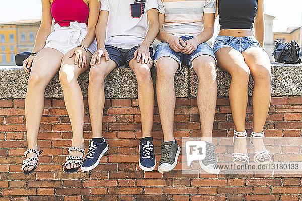 Beine von Freunden  die zusammen an einer Wand sitzen