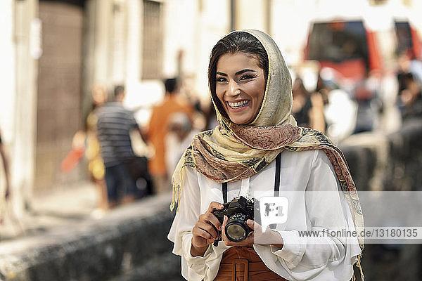 Spanien  Granada  junge arabische Touristin mit Hidschab  die während der Besichtigung der Stadt eine Kamera benutzt
