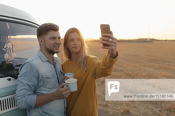 Junges Paar beim Selbstfahren im Wohnmobil in ländlicher Landschaft bei Sonnenuntergang