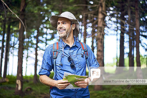 Smiling man holding a map hiking in the forest