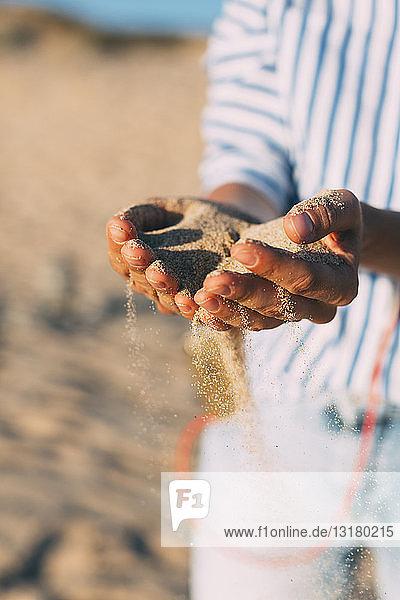 Frau am Strand  die Sand durch ihre Hände rieseln lässt  Nahaufnahme