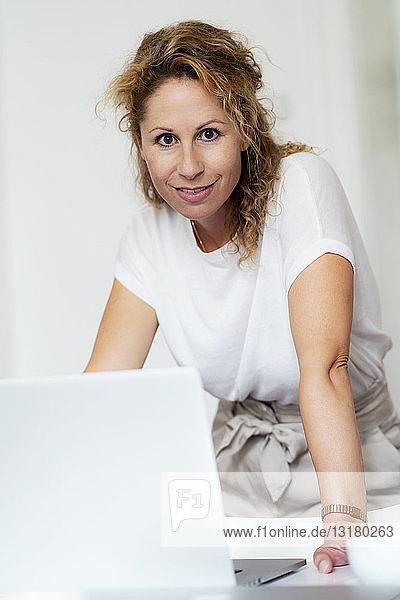 Porträt einer lächelnden Frau mit Laptop