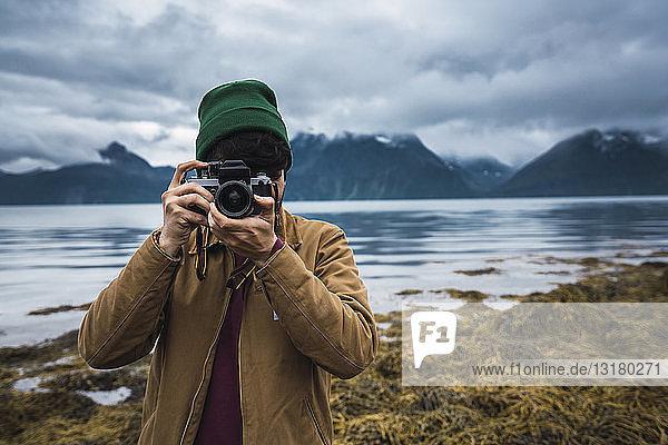 Junger Mann mit Wollmütze beim Fotografieren mit der Kamera