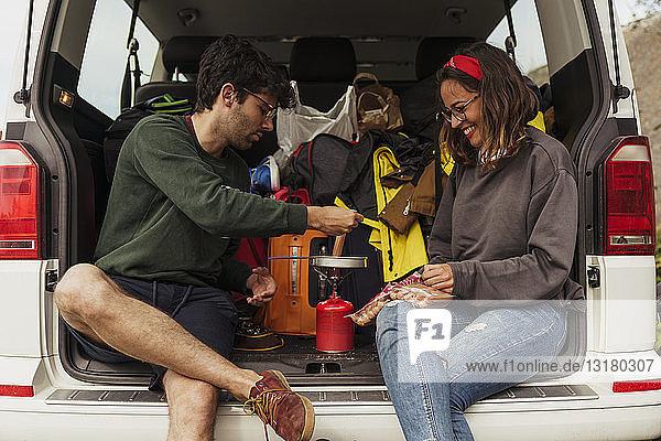 Junges Paar bereitet Würstchen auf einem Campingkocher zu