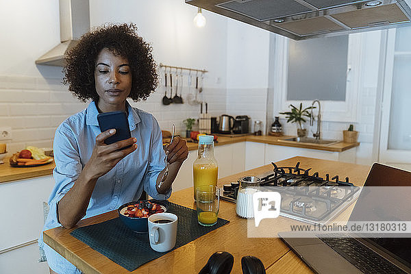 Woman having breakfast in her kitchen  using smartphone