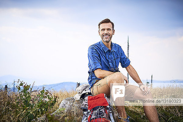Portrait of smiling man resting during hiking trip
