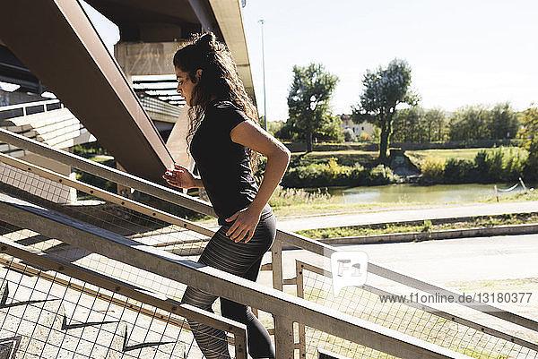 Sportliche junge Frau rennt auf Treppen