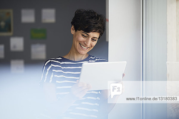 Smiling woman with tablet at the window