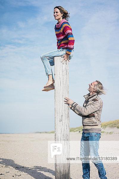 Reifer Mann hilft Frau beim Klettern auf einen Holzpfahl am Strand