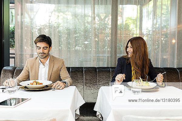 Lächelnde Frau schaut Mann in einem Restaurant an