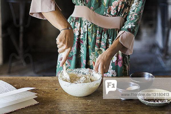 Junge Frau bei der Zubereitung von Kuchenteig  Teilansicht