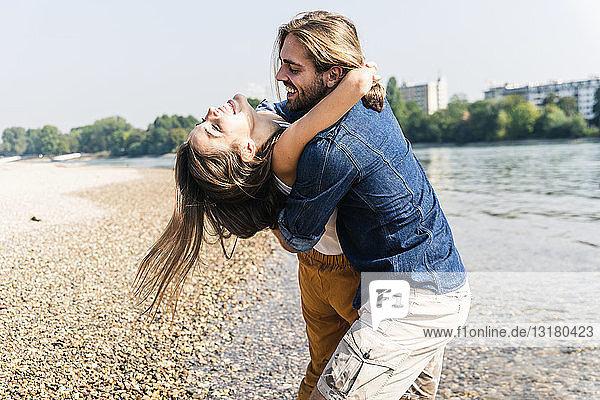 Glückliches junges verliebtes Paar umarmt sich am Flussufer