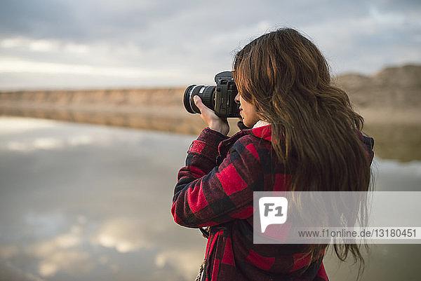 Junge Frau beim Fotografieren mit Kamera am Strand