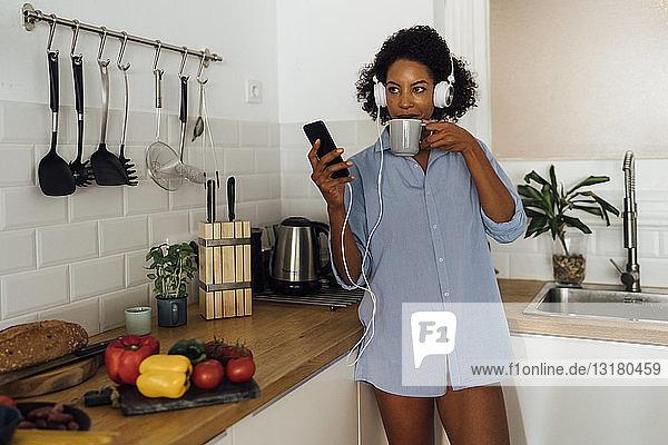 Frau mit Kopfhörern  die ein Smartphone benutzt und Kaffee zum Frühstück in ihrer Küche trinkt
