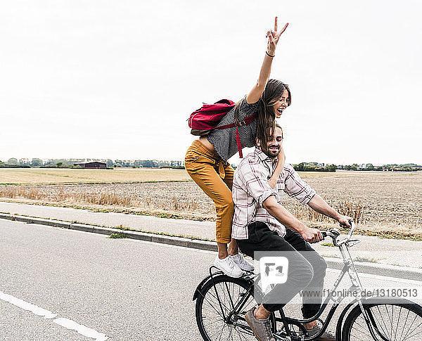 Glückliches junges Paar fährt gemeinsam auf einem Fahrrad auf der Landstraße