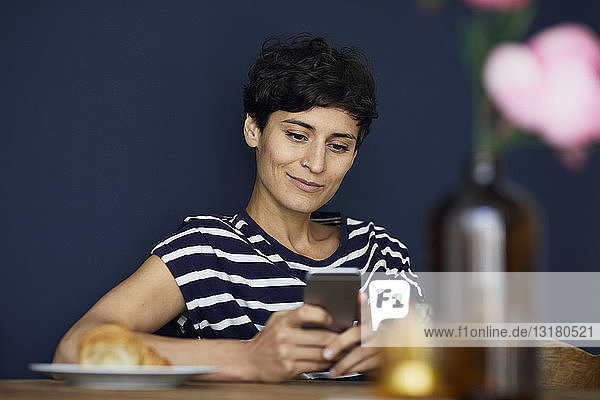 Smiling woman at home sitting at wooden table checking cell phone
