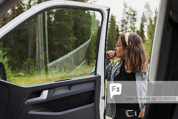 Finland  Lapland  young woman at a car in rural landscape