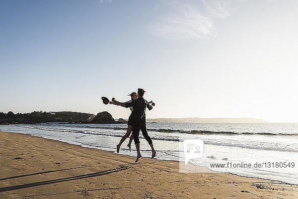 Frankreich  Bretagne  glückliches junges Paar springt bei Sonnenuntergang an den Strand