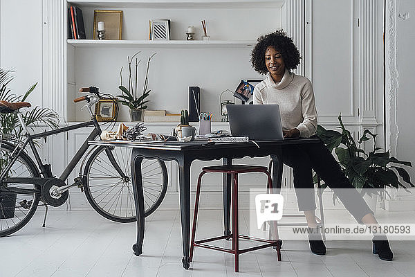 Mid adult woman working in her home office  using laptop