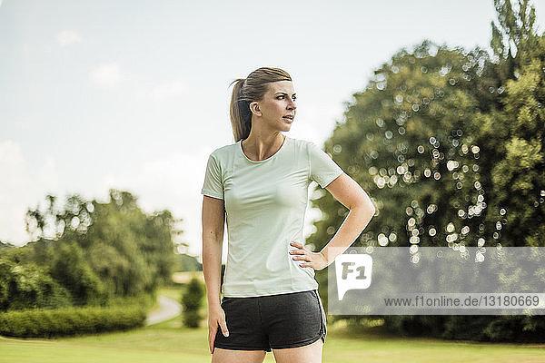 Sportliche junge Frau  die in einem Park steht und zur Seite schaut