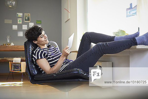 Relaxed woman using tablet at home