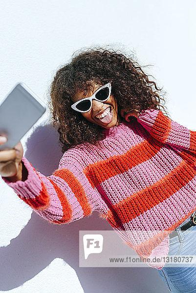 Porträt einer jungen Frau mit Sonnenbrille  die sich mit dem Handy selbstständig macht