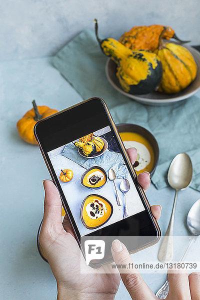 Frauenhände beim Fotografieren von Schüsseln mit hausgemachter Kürbissuppe
