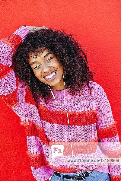 Porträt einer lachenden jungen Frau mit Kopfhörern vor roter Wand