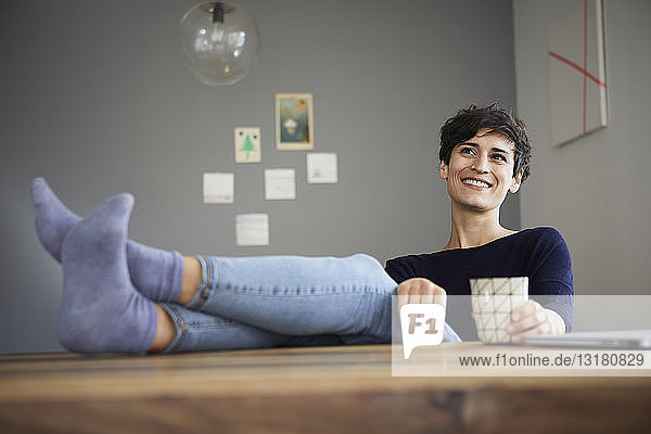 Smiling woman at home sitting at table with cup of coffee