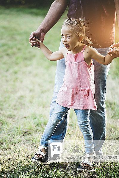Mädchen geht auf der Wiese auf den Füßen des Vaters