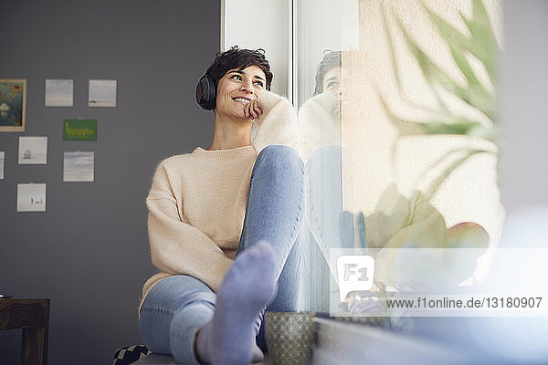 Smiling woman at home wearing headphones sitting at the window