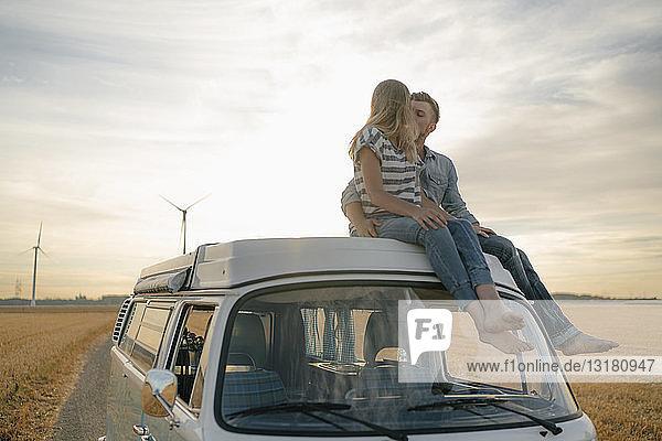 Pärchen küsst sich auf dem Dach eines Wohnmobils in ländlicher Landschaft