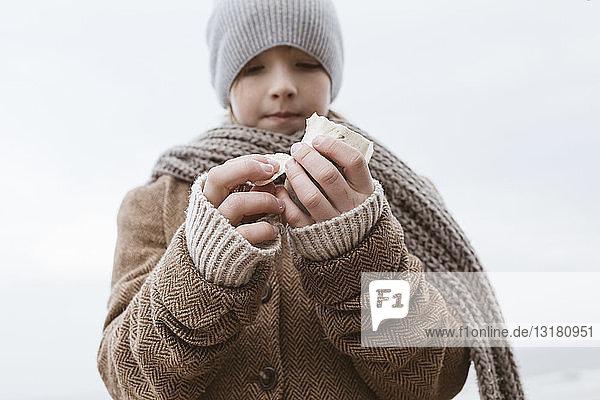 Boy's hands holding cuttlebone on the beach in winter