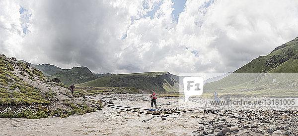 Russia  Caucasus  Mountaineers crossing river in Upper Baksan Valley