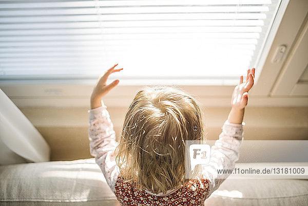 Rückenansicht eines blonden kleinen Mädchens am Fenster  das mit Sonnenlicht spielt