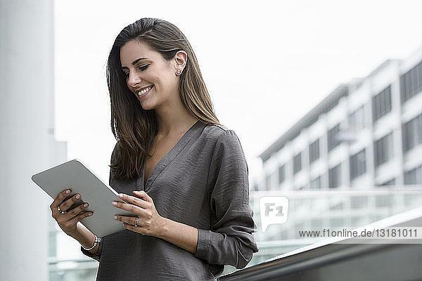 Lächelnde junge Geschäftsfrau benutzt digitales Tablet im Freien