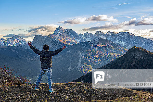 Italy  South Tyrol  Seiser Alm  Hiker in front of Seceda and Sass Rigais at sunrise