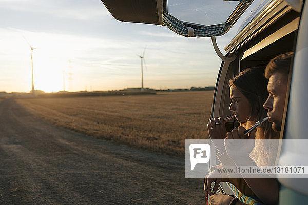 Ehepaar beim Zähneputzen im Wohnmobil in ländlicher Landschaft bei Sonnenuntergang