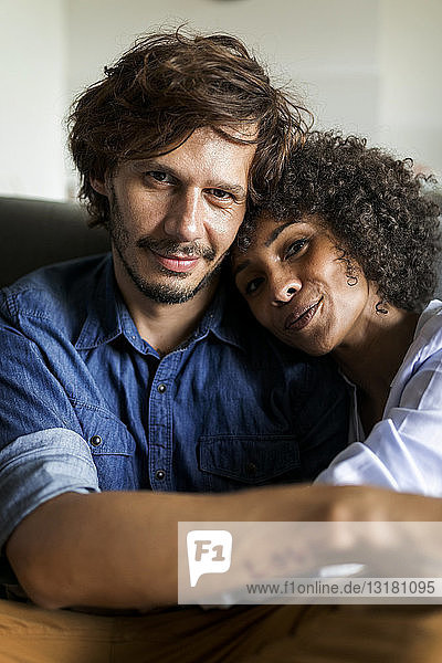 Portrait of smiling couple sitting on couch
