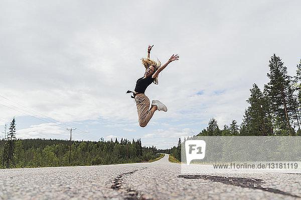 Finnland  Lappland  ausgelassene junge Frau springt in ländlicher Landschaft