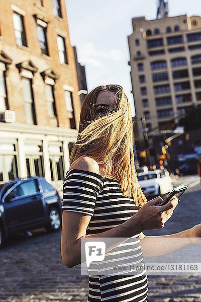 USA  New York  Brooklyn  Dumbo  Frau mit Handy auf der Straße