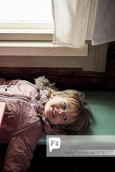 Porträt eines lächelnden kleinen Mädchens  das auf einer Holzbank liegt und im Haus einen Anorak trägt
