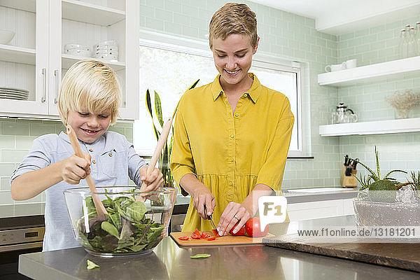 Lächelnde Mutter und Sohn bereiten gemeinsam Salat in der Küche zu