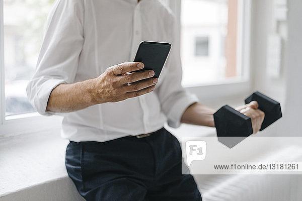 Erfolgreicher Manager mit Smartphone und Training mit einer Hantel