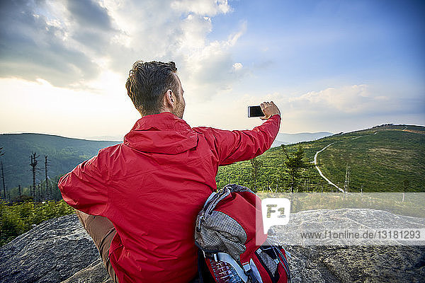 Man sitting on rock taking picture with his cell phone during hiking trip in the mountains