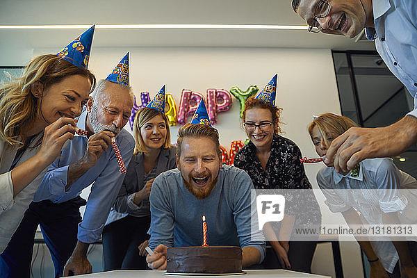 Kollegen mit einer Geburtstagsfeier im Büro mit Kuchen  Partyblower und Partyhüten