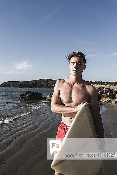 Frankreich  Bretagne  junger Mann mit Surfbrett am Meer stehend
